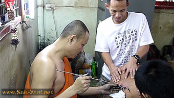The monk is engraving the tattoo